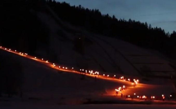 Ski instructors in torch light descent