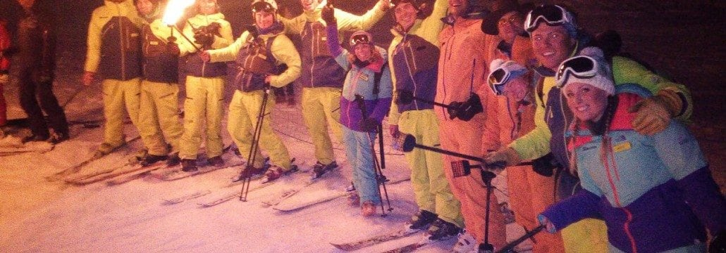 Ski instructors carrying torches in Courchevel